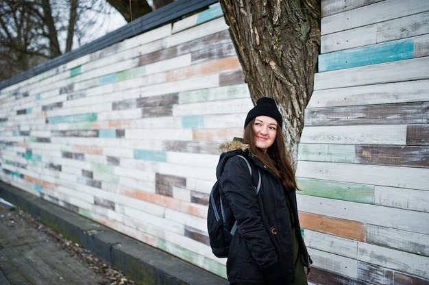 Chica joven usar sombreros negros contra la pared de madera.