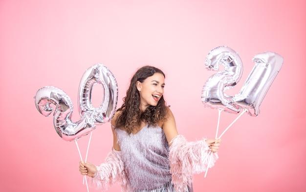 Chica joven vestida de forma festiva riendo sobre un fondo rosa con globos de navidad plateados para el concepto de año nuevo