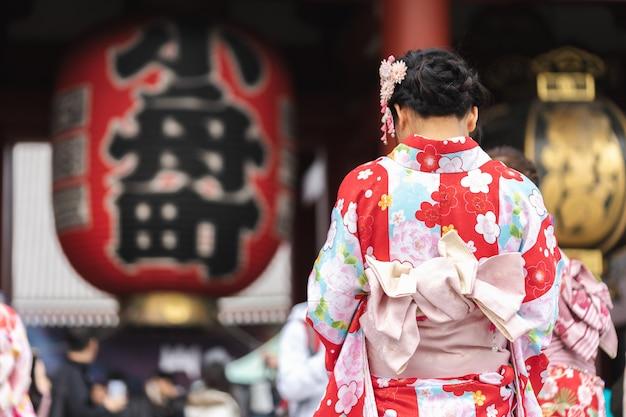 Chica joven vestida con un kimono japonés parado frente al templo sensoji en tokio,