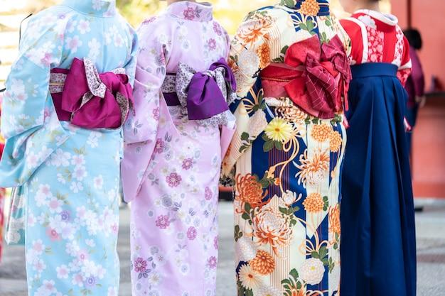 Chica joven vestida con un kimono japonés de pie frente al templo sensoji