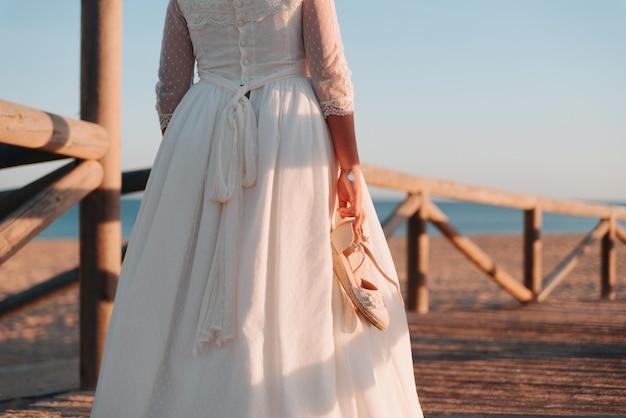 Chica joven en un vestido caminando con sus zapatos en la mano sobre un rompeolas de madera