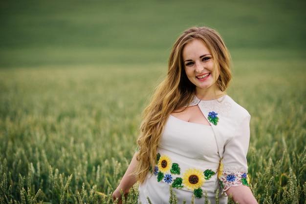 La chica joven en el vestido nacional ucraniano presentó en el campo de la guirnalda.