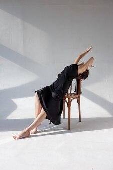 Chica joven en vestido negro posa en silla en blanco