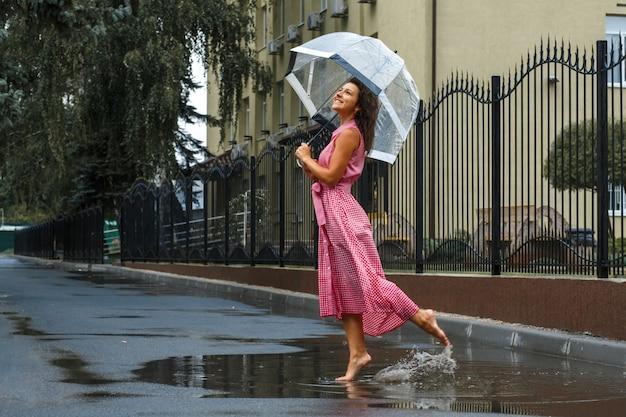 Chica joven en un vestido rojo con un paraguas transparente bailando bajo la lluvia de pie en un charco