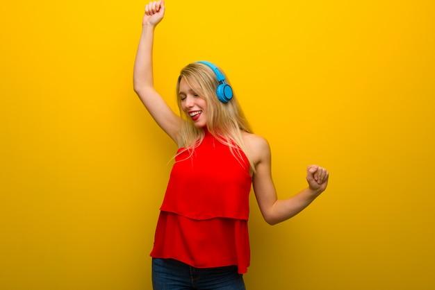 Chica joven con vestido rojo sobre pared amarilla escuchando música con auriculares y bailando