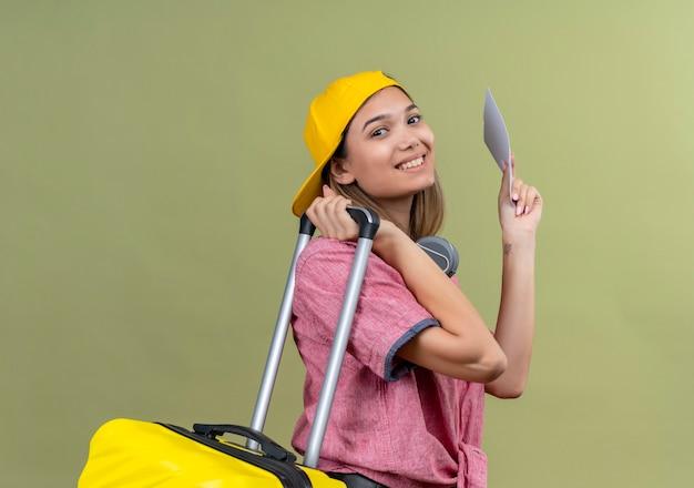 Chica joven viajero con camisa rosa en la gorra con auriculares alrededor del cuello sosteniendo la maleta y los billetes de avión sonriendo alegremente listo para viajar