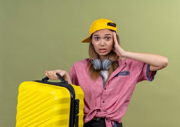 Chica joven viajero con camisa rosa en la gorra con auriculares alrededor del cuello sosteniendo la maleta mirando confundido y muy ansioso con la mano en la cabeza