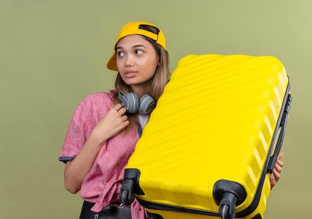 Chica joven viajero con camisa rosa en gorra con auriculares alrededor del cuello sosteniendo maleta mirando confundido