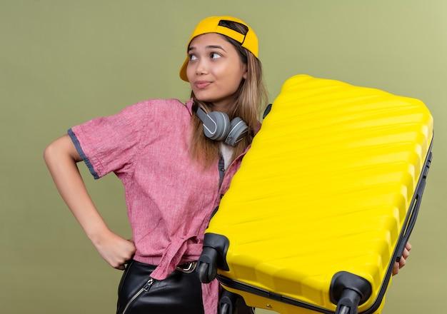 Chica joven viajero vistiendo camisa rosa en gorra con auriculares alrededor del cuello sosteniendo la maleta mirando a un lado sonriendo