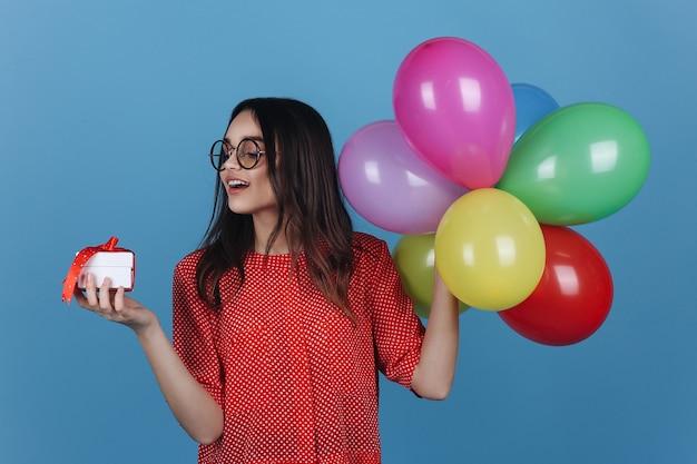 La chica joven en vidrios se coloca con un pequeño presente y globos