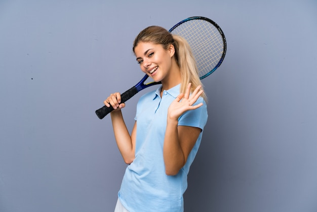 Chica de jugador de tenis adolescente sobre pared gris saludando con la mano con expresión feliz