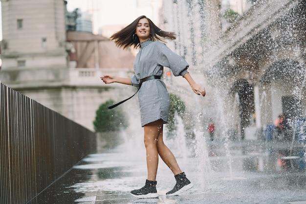 Chica jugando y bailando en una calle mojada