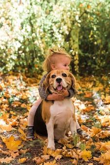 Chica jugando con su mascota en el bosque