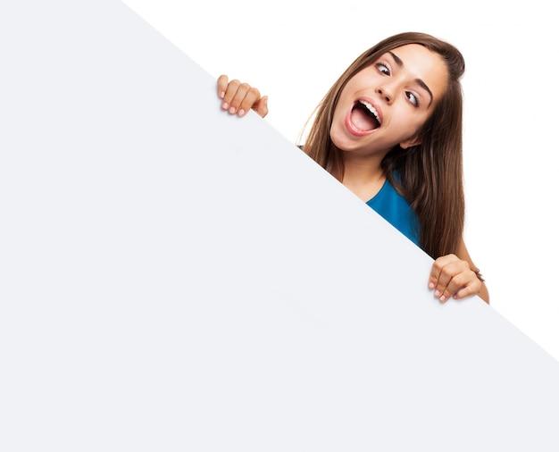 Chica juguetona con una cartel en blanco