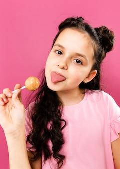 Chica juguetona con lengua afuera comiendo piruleta