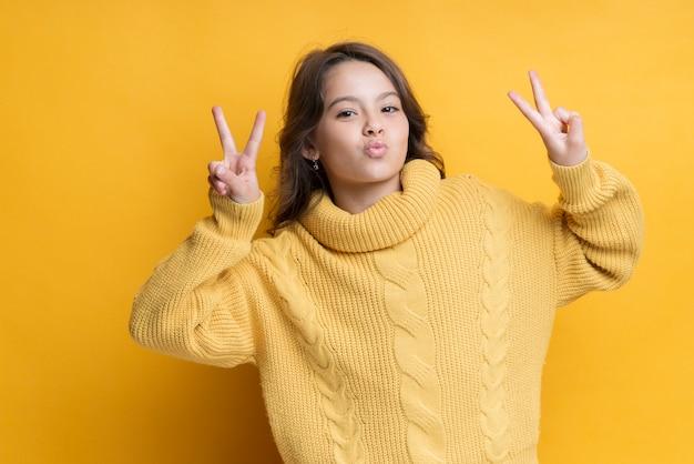 Chica juguetona mostrando retrato de signo de la paz