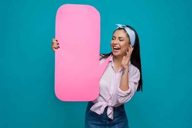 Chica juguetona posando con el bocadillo de diálogo de papel.