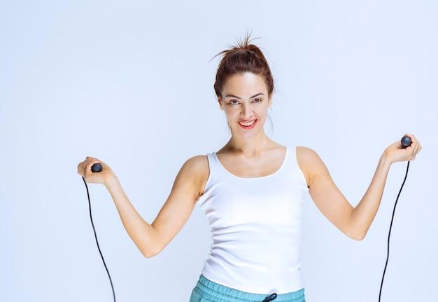 Chica juguetona sosteniendo una cuerda de saltar azul y saltando sobre ella.