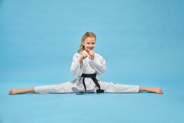 Chica en kimono blanco con cinturón negro en posición de combate.