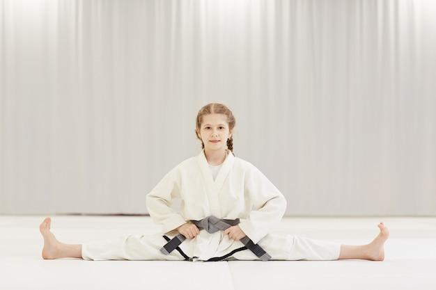 Chica en kimono haciendo ejercicios de estiramiento
