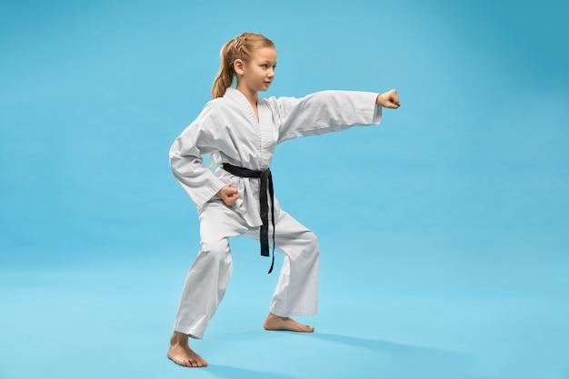Chica en kimono de pie en posición y golpeando con la mano.