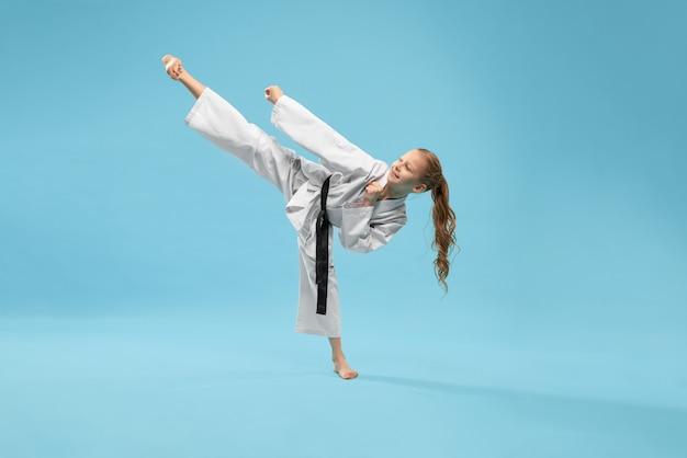 Chica en kimono practicando patada hacia adelante.