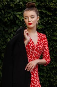 Chica con labios rojos, maquillaje de noche en un vestido rojo con estampado y chaqueta negra, estilo de ropa urbana
