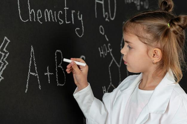 Chica en laboratorio con abrigo escribiendo