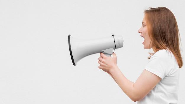 Chica de lado gritando en megáfono