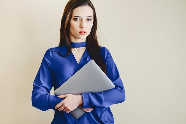 Chica con laptop en el fondo de la pared