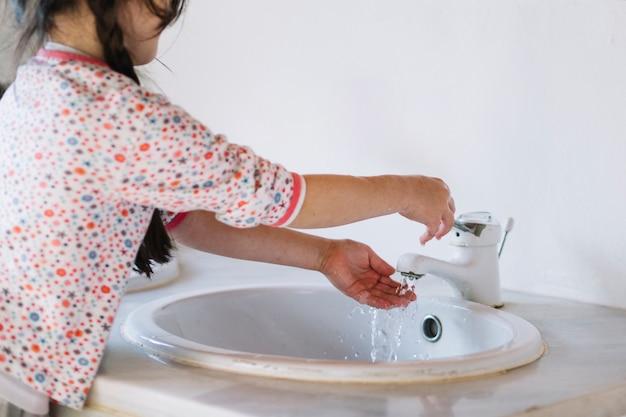 Chica lavando la mano en el baño