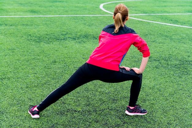 Chica con leggings deportivos negros y una chaqueta rosa amasa antes de entrenar en un campo deportivo abierto