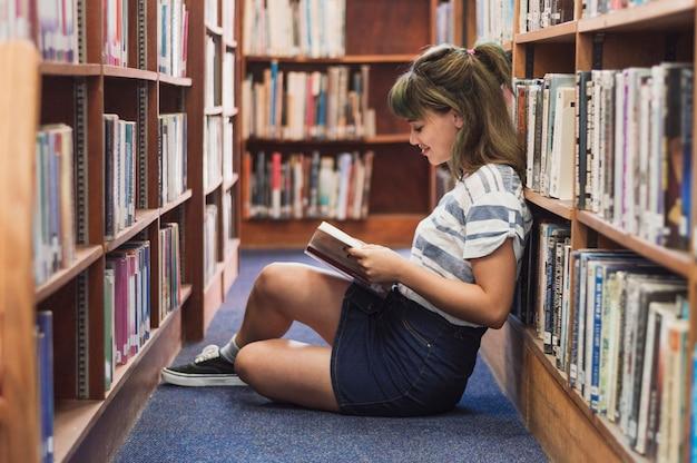 Chica leyendo en una biblioteca