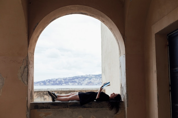 Chica leyendo un libro boca arriba