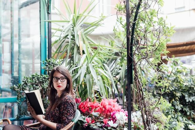 Chica leyendo un libro en una cafetería