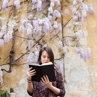 Chica leyendo un libro en la calle