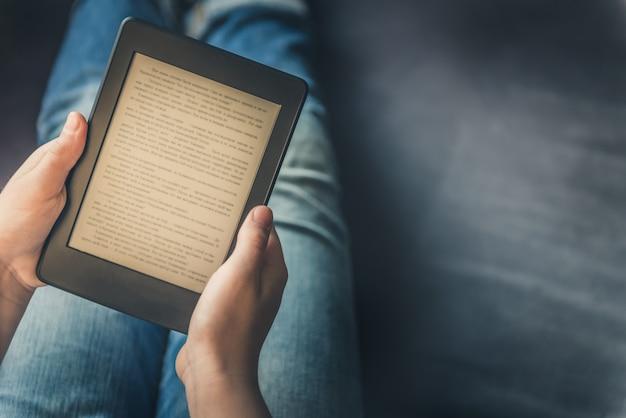 Chica está leyendo un libro electrónico en dispositivo de tableta digital