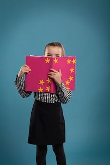 Chica leyendo un libro en una portada rosa, disparando en el estudio