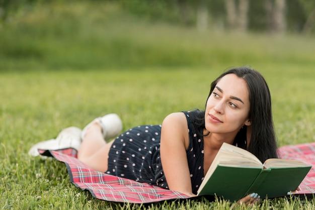 Chica leyendo sobre manta de picnic