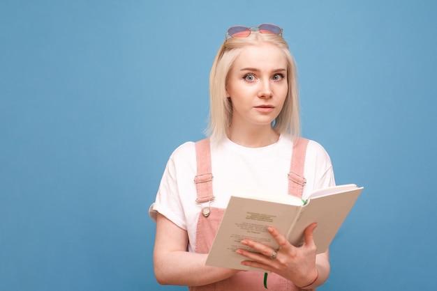 Chica con un libro de manos de pie en azul con cara de asombro.