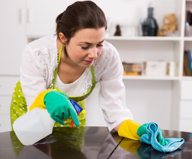 Chica limpia mesa en casa