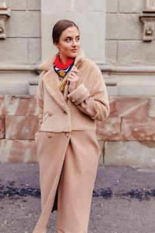 Chica linda con estilo joven en un abrigo de piel paseando por la ciudad cerca de casas de madera y paredes de piedra