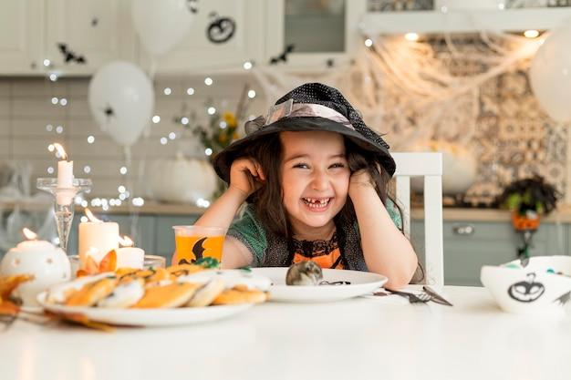 Chica linda y feliz con disfraz de bruja