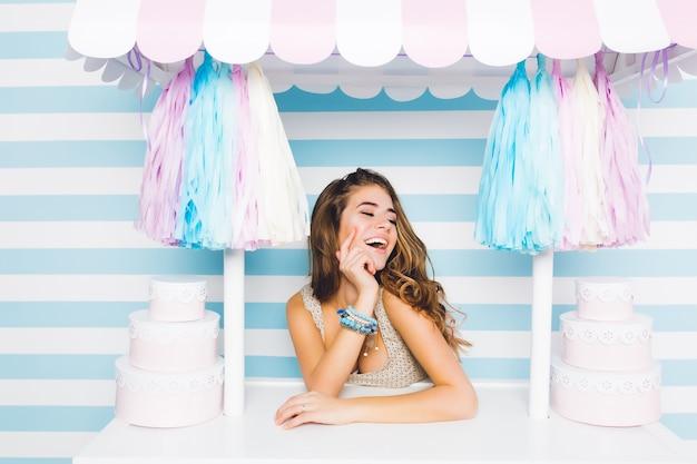 Chica linda de pelo largo inspirada en accesorios azules de moda sentada detrás del mostrador con postres en la pared rayada. vendedor de sexo femenino encantador feliz riendo posando en la tienda de dulces con los ojos cerrados.