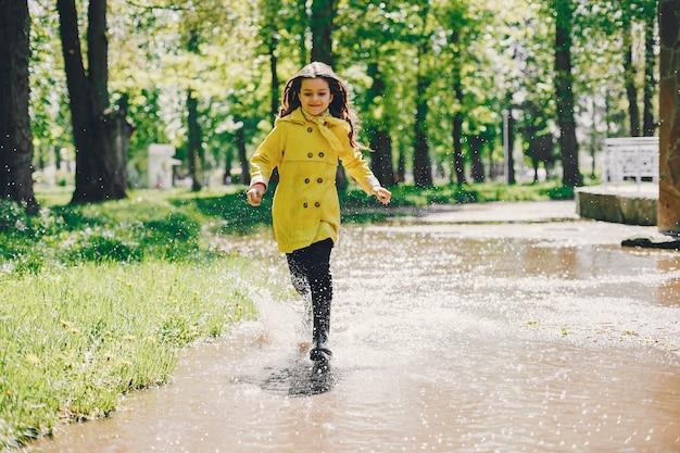 Chica linda plaiyng en un día lluvioso