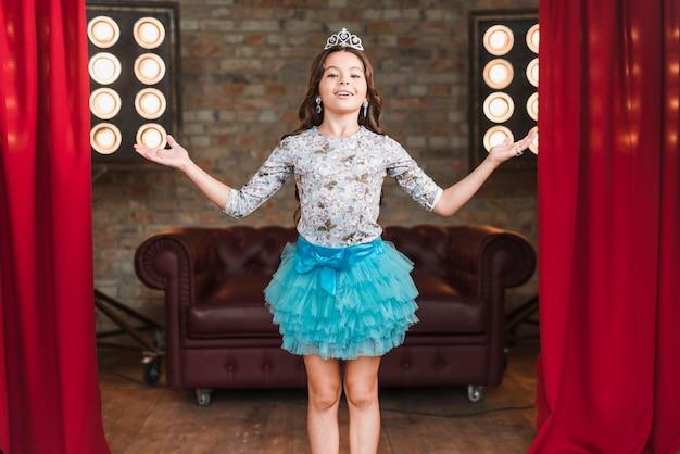 Chica en lindo vestido y corona que presenta en el escenario