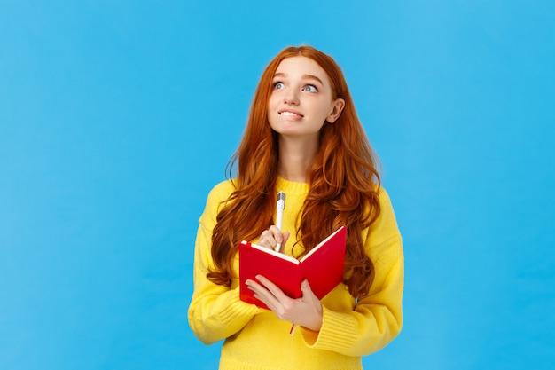 Chica llena de esperanzas y aspiraciones escribiendo deseos en el cuaderno. mujer pelirroja atractiva inspirada y creativa que mira la esquina superior izquierda soñadora y esperanzada, sostenga la pluma y el diario, sonriendo