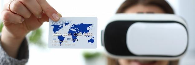 Chica lleva gafas virtuales, muestra tarjeta de crédito