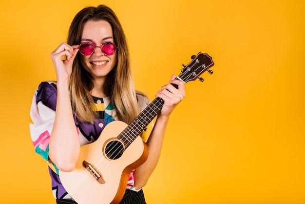 Chica llevando gafas con un ukelele
