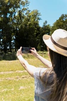 Chica llevando sombrero haciendo un selfie